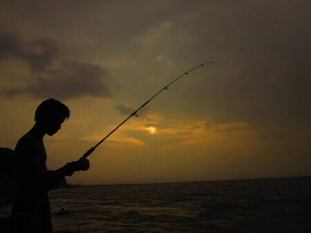 Boy fishing at sunset   photo