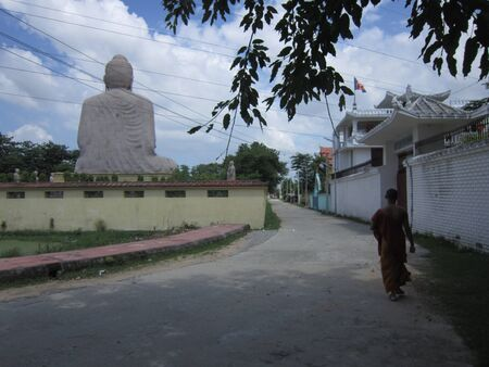 Monk walking behind 80 feet Lord Buddha Statue at Bodhgaya. Shot at 0134 pm on 10.08.12 at Bodhgaya, Bihar, India, Asia.