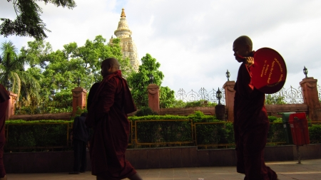 Monks walking past Mahabodhi temple, Bodhgaya to attend prayer at temple. Shot at 1652 pm on 10.08.12 at Bodhgaya, Bihar, India, Asia. Stock Photo - 14816186