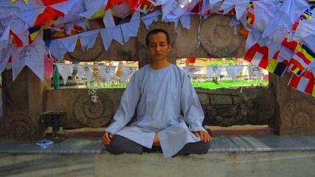 A tourist pilgrim meditating at Bodhgaya Mahabodhi temple. Shot at 1708 pm on 10.08.12 at Bodhgaya, Bihar, India, Asia.