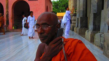 Monk talking on mobile at Mahabodhi temple complex, Bodhgaya, Shot at 1712 pm on 10.08.12 at Bodhgaya, Bihar, India, Asia. Stock Photo - 14816184