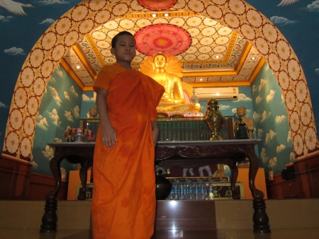 A boy monk looking at the visitors at a temple at Bodhgaya. Shot at 0641 am on 11.08.12 at Bodhgaya, Bihar, India, Asia.