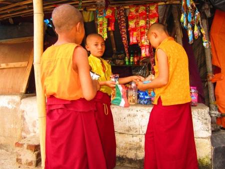 Children monk with INDIAN NATIONAL FLAG ahead of Independence day of India at a grocery shop in front of Karma Monastaery, Bodhgaya, Shot at 1754 pm on 11.08.12 at Bodhgaya, Bihar, India, Asia.
