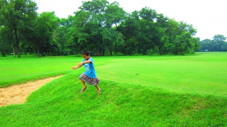 kid running in golf course Stock Photo