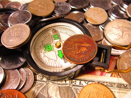time deficit: COMPASS IN COINS AND INTERNATIONAL MONEY Stock Photo