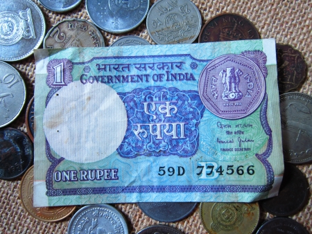 ONE RUPEE NOTE OF INDIA AMONG COINS OF DIFFERENT COUNTRIES photo