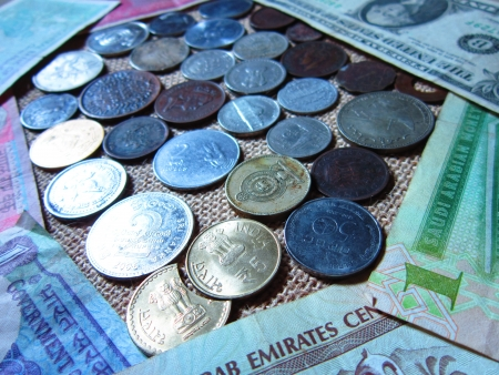 moksha: COINS OF DIFFERENT COUNTRIES SURROUNDED BY MONEY OF DIFFERENT COUNTRIES  Stock Photo