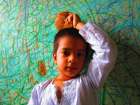 KID POSING WITH COCONUT AT HER HEAD photo