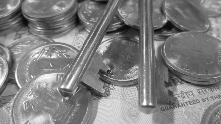 financial sector: KEY ON MONEY AND COINS-SAVINGS CONCEPT  BLACK AND WHITE