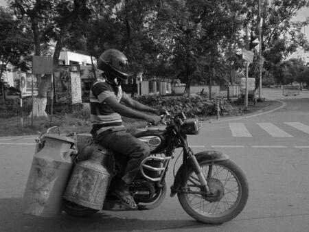 milkman: MILKMAN CARRYING MILK AT MOTORCYCLE. SHOT AT PATNA, BIHAR, INDIA, ASIA ON AFTERNOON 09.09.12