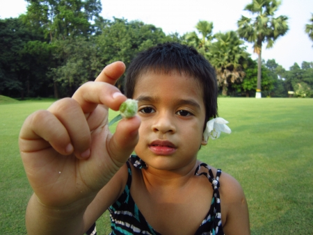 KID SHOWING BUDS IN FRONT OF FACE