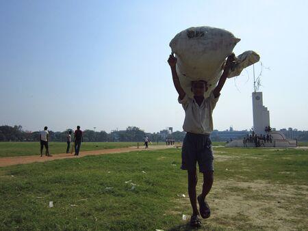 maidan: LABOURER CARRYING BAGS. PEOPLE ACTIVITIES AT GANDHI MAIDAN. SHOT AT MORNING HOURS ON 16.10.2012 AT  GANDHI MAIDAN PATNA, BIHAR, INDIA