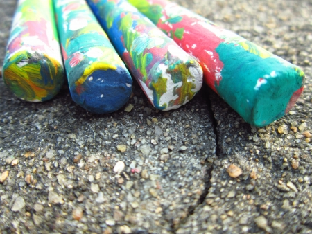 lined up: COLORFUL CHALKS LINED UP ON ROUGH GROUND-EDUCATIONAL CONCEPT