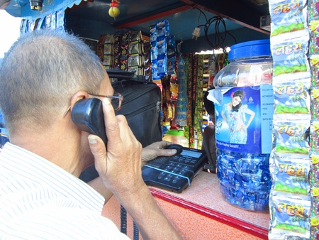 bihar: MAN CALLING AT PHONE FROM A ROADSIDE TELEPHONE BOOTH. SHOT AT AFTERNOON HOURS ON 30.10.12 AT PATNA, BIHAR, INDIA. Editorial