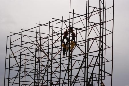 erecting: LABOURERS ERECTING ADVERTISEMENT IN BILLBOARD. SHOT AT MORNING HOURS ON 18.06.2011 AT PATNA, BIHAR, INDIA