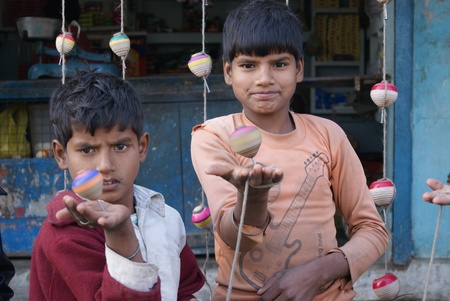 STREET CHILDREN PLAYING WITH LATTU OR TOPS. SHOT AT MORNING HOURS AT BITHOOR, UTTAR PRADESH, INDIA, ASIA.