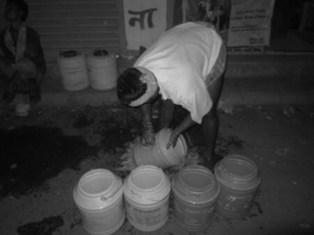 milkman: MILKMAN CLEANING MILKCARRIER. SHOT IN BLACK AND WHITE.SHOT AT EVENING HOURS ON 02.11.12 AT PATNA, BIHAR, INDIA.
