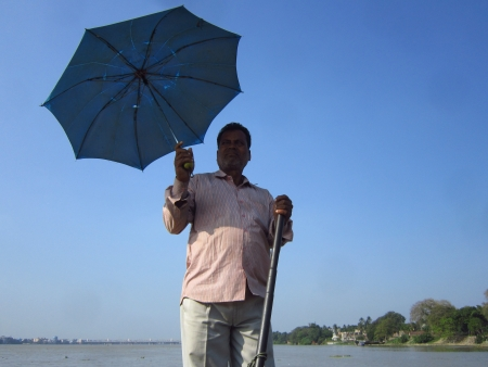 calcutta: OARSMAN  HOLDING UMBRELLA OVER HIS HEAD. SHOT AT CALCUTTA, INDIA: AFTERNOON HOURS ON NOVEMBER 14,2012.