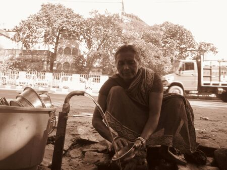 calcutta: WOMAN WASHING DISH ON STREET.SHOT AT CALCUTTA, INDIA: AFTERNOON HOURS ON NOVEMBER 15,2012.