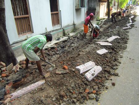labourers: LABOURERS DIGGING ROAD FOR LAYING OUT ELECTRICAL CABLES.SHOT AT CALCUTTA, INDIA:AFTERNOON HOURS ON NOVEMBER 18,2012.