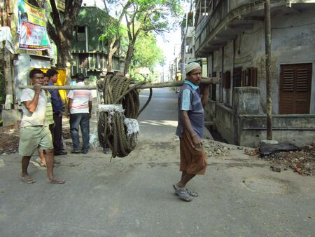 labourers: LABOURERS CARRYING ELECTRICAL WIRES FOR LAYING.SHOT AT CALCUTTA, INDIA:AFTERNOON HOURS ON NOVEMBER 18,2012. Editorial