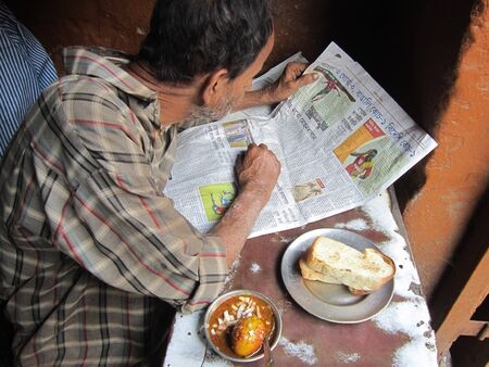 calcutta: MAN READING NEWSPAPER AND EATING SNACKS.SHOT AT CALCUTTA, INDIA: MORNING HOURS ON NOVEMBER 18,2012. Editorial