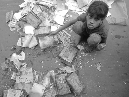 calcutta: GIRL SEARCHING AMONG OLD BOOKS.SHOT AT CALCUTTA, INDIA:AFTERNOON  HOURS ON NOVEMBER 13,2012.