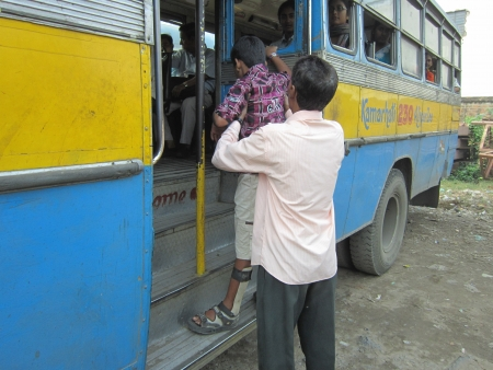 physically: MAN CARRYING PHYSICALLY CHALLENGED IN A BUS.SHOT AT CALCUTTA INDIA: MORNING HOURS ON NOVEMBER 12,2012. Editorial