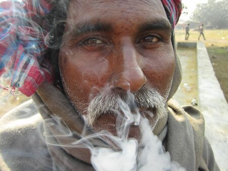 sonepur fair: MAN SMOKING.SHOT DURING MORNING HOURS ON 02.12.12 AT SONEPUR FAIR, SONEPUR, BIHAR, INDIA.