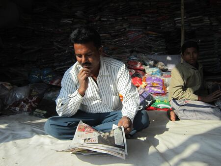 MAN READING NEWSPAPER AT STALL.SHOT DURING MORNING HOURS ON 02.12.12 AT SONEPUR FAIR, SONEPUR, BIHAR, INDIA.