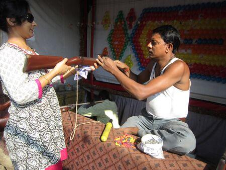 sonepur: WOMAN TRYINH HANDS IN GUN.SHOT DURING MORNING HOURS ON 02.12.12 AT SONEPUR FAIR, SONEPUR, BIHAR, INDIA.