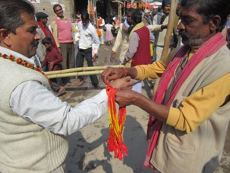 bihar: MAN TYING RELIGIOUS THREAD TO DEVOTEE.SHOT DURING MORNING HOURS ON 02.12.12 AT SONEPUR FAIR, SONEPUR, BIHAR, INDIA. Editorial