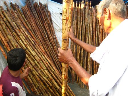 MAN PURCHASING BAMBOO STICK AT FAIR.SHOT DURING AFTERNOON HOURS ON 02.12.12 AT SONEPUR FAIR, SONEPUR, BIHAR, INDIA. Editorial