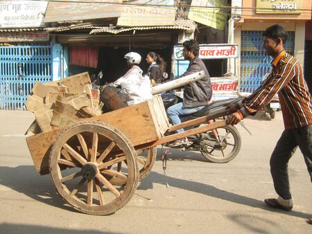 pushes: UNIDENTIFIED MAN PUSHES CART WITH WASTE ITEMS. SHOT ON MORNING HOURS ON FEBRUARY 14, 2013 AT PATNA, BIHAR, INDIA.