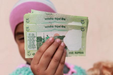 balanced budget: Girl shows Indian money.