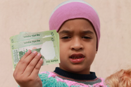 international trade commission: Girl shows Indian money.