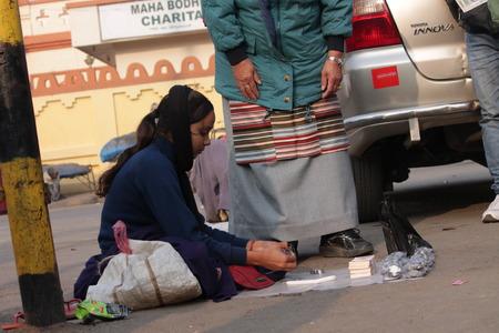 bodhgaya: Woman sell Indian money on road. Shot at Bodhgaya, India, afternoon hours on 26.12.14 Editorial