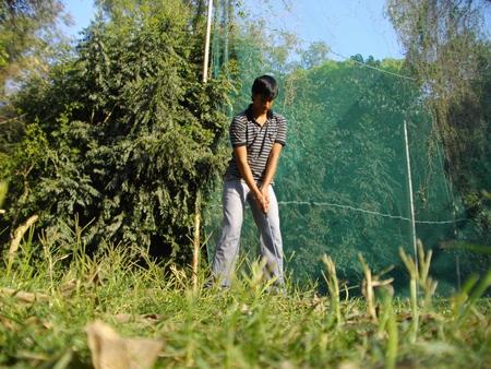 plays: Indian boy plays golf.