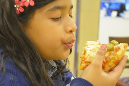Indian girl eats Pizza. Jan 2018. Zdjęcie Seryjne