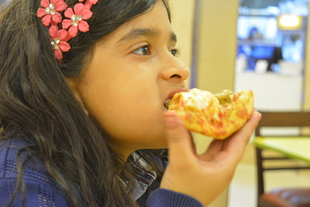 Indian girl eats Pizza