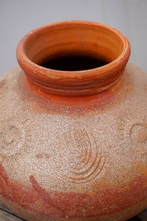 A close up shot of a clay pot.Pottery is the process of forming vessels and other objects with clay and other ceramic materials, which are fired at high temperatures to give them a hard, durable form.