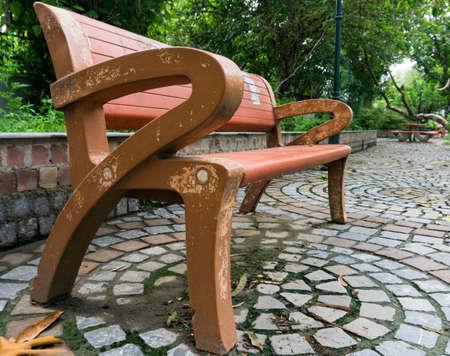 An empty park bench on a roadside. 免版税图像
