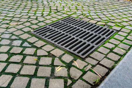 A large water drainage on the footpath with metal cover.