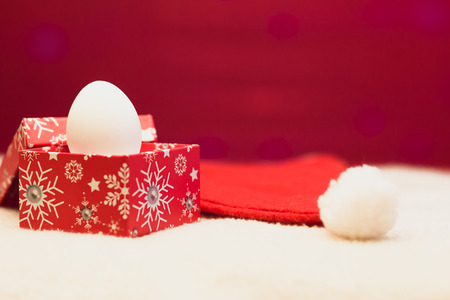 Happy new year / Marry Christmas White egg in red box on red-white background and red hat of Santa Claus with white pompon