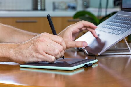 Male designer hands using a drawing graphics tablet and a laptop while working at home. Banco de Imagens