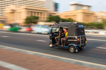COLOMBO, SRI LANKA - February 19, 2019: A motorcycle Tuk Tuk with passengers, blurry speed motion in Colombo, Sri Lanka.