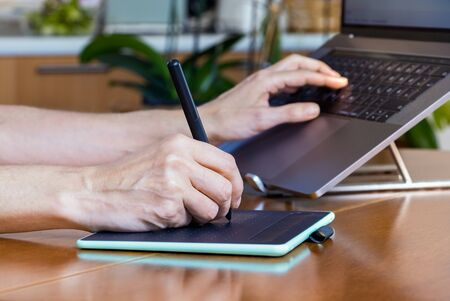 Female designer hands using a drawing graphics tablet and a laptop while working at home.
