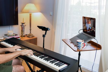 Male piano teacher giving piano lessons online at home using a laptop and a smarphone a smartphone on a gimbal as second camera.