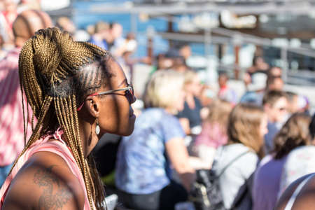 Cape Town, South Africa - January 2th, 2019: A south african black woman with braid hair and blond dyed watching a show at the amphitheater of the V & A whaft, Cape Town.