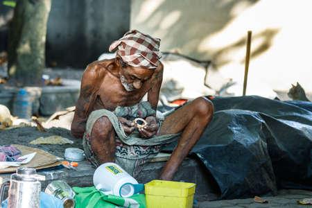 Galle, Sri Lanka - February 18th, 2019: Portrait of a senior homeless sri lankan man wearing a turban looking a piece of garbage sitting in the street in Galle, Sri Lanka.
